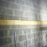 Construction d'un plancher en bois : la poutre fixée au mur